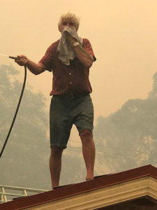 Shoalhaven resident Ian Harp hoses down the roof of his home on New Year's Eve 2020, as the fires approach
